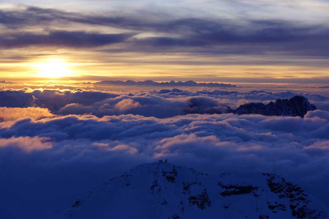 Above the clouds on the Piz Boè, in the background the peak of the Sassolungo in winter